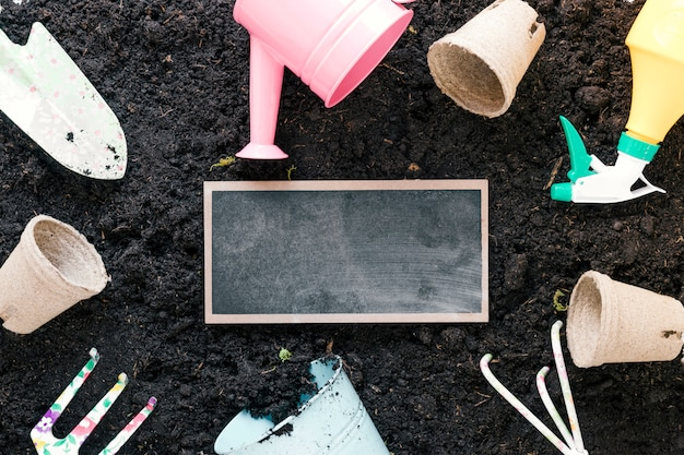 High angle view of gardening tools and blank slate arranging over black dirt Free Photo
