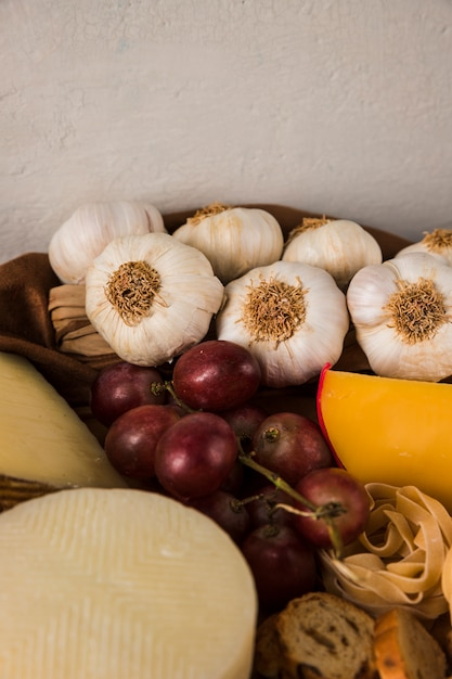 High angle view of garlic; grape; raw pasta and cheese Free Photo