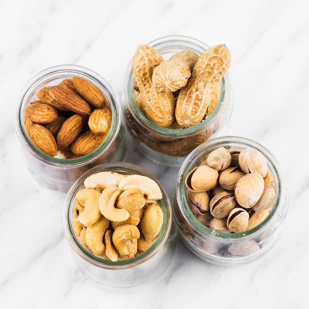 High angle view of glass jars filled with nut food on marble surface Free Photo