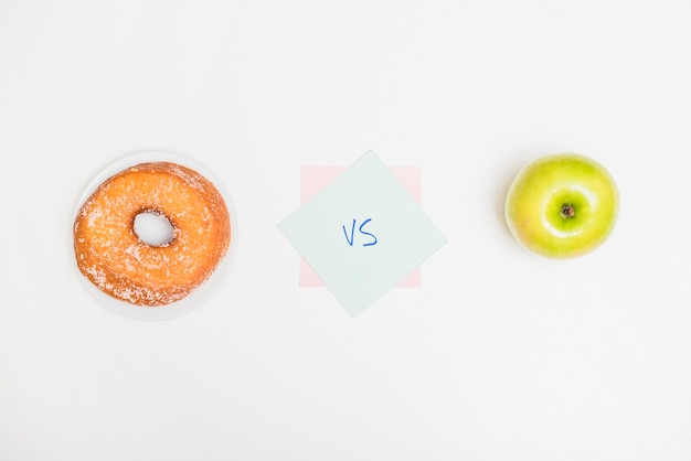 High angle view of green apple versus donut on white backdrop Free Photo
