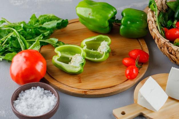 ハイアングルピーマントマト、塩、チーズ、灰色の表面に野菜とまな板の上半分にカット 無料写真