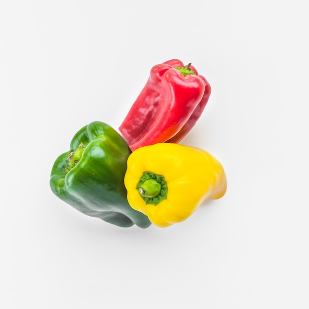 High angle view of green; yellow and red bell peppers on white background Free Photo