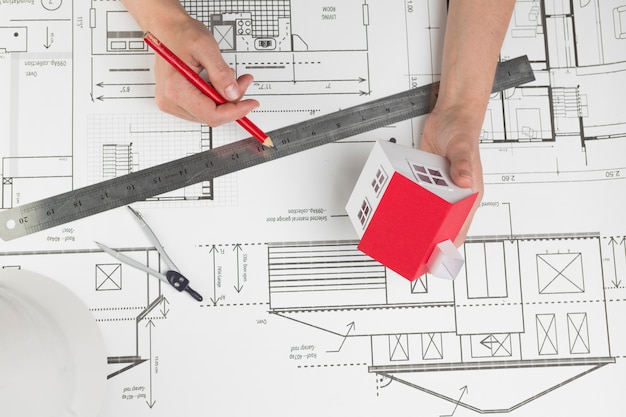 High angle view of hand holding small house model and pencil over blueprint Free Photo