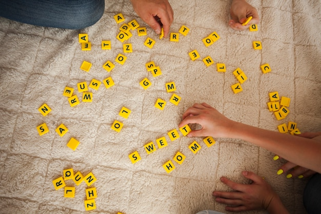 High angle view of hand playing scrabble game on carpet Free Photo