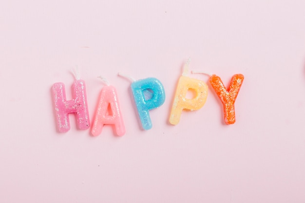 High angle view of happy word candles on pink background Free Photo