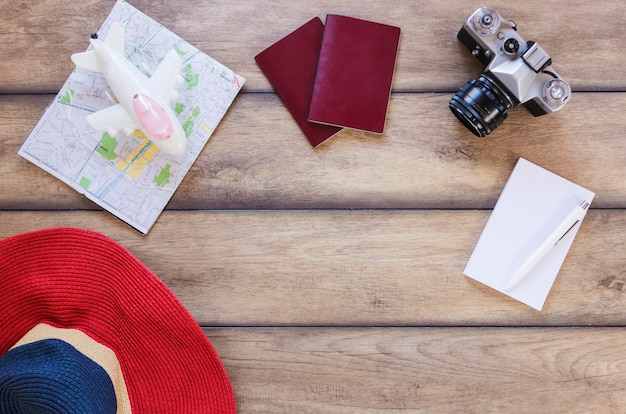 High angle view of hat; map; airplane; passport; camera; paper and pain on wooden surface Free Photo