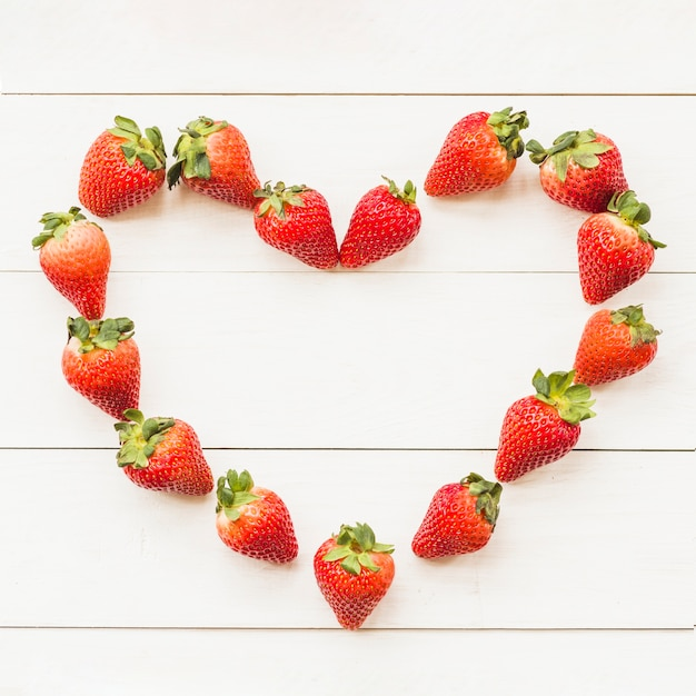 High angle view of heart shape made up of juicy strawberries Free Photo