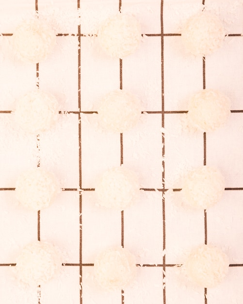 High angle view of homemade coconut chocolate arranged on a row over white checkered table cloth Free Photo