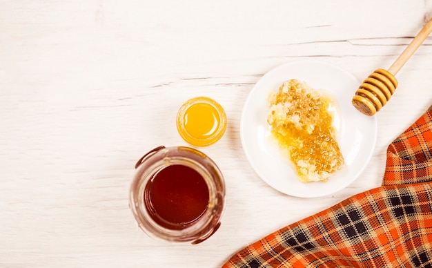 High angle view of honeycomb and honey jar Free Photo