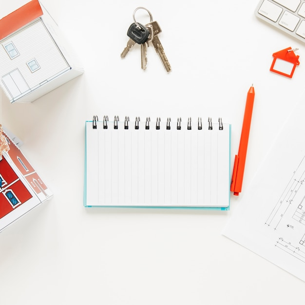 High angle view of house model near spiral notepad with keys and pen over white background Free Photo