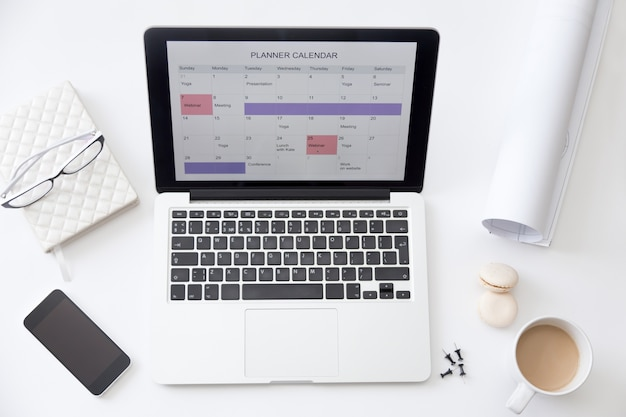 Calendar Planner For Laptop : High angle view image of desk planner calendar on laptop