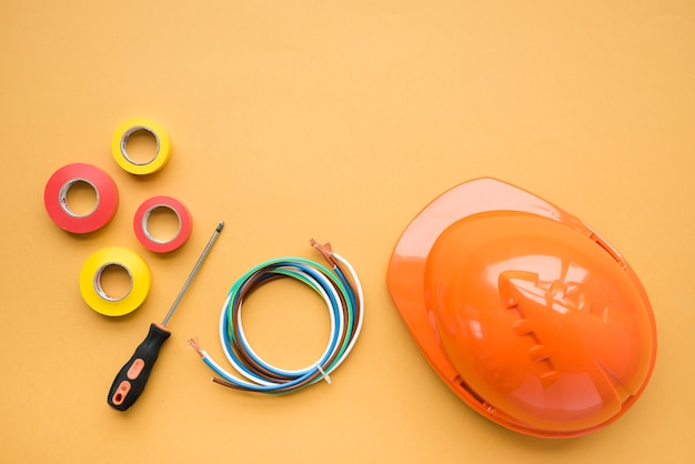 High angle view of insulating tape; screwdriver; wire and orange hard hat over yellow backdrop Free Photo