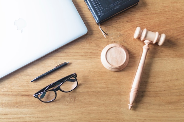 High angle view of laptop; spectacles; gavel and pen on wooden background on wooden desk Free Photo