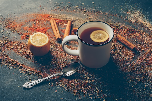 High angle view lemon tea and dried herbs with dry cinnamon, spoon and lemon Free Photo