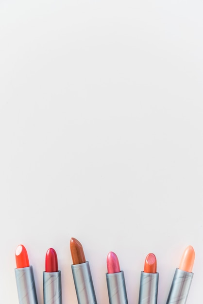 High angle view of lipsticks shades on white background arranged in a row Free Photo