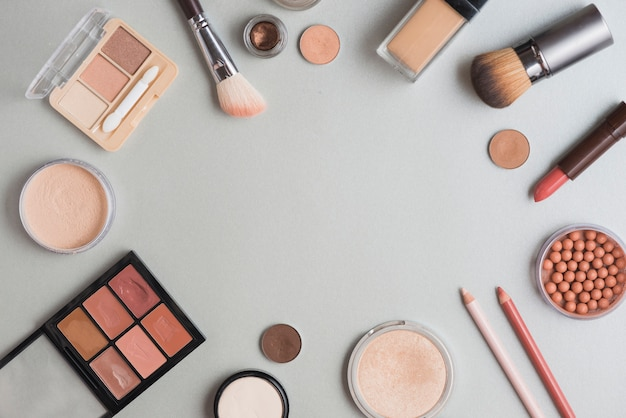 High angle view of make up kits forming circular shape on white backdrop Free Photo