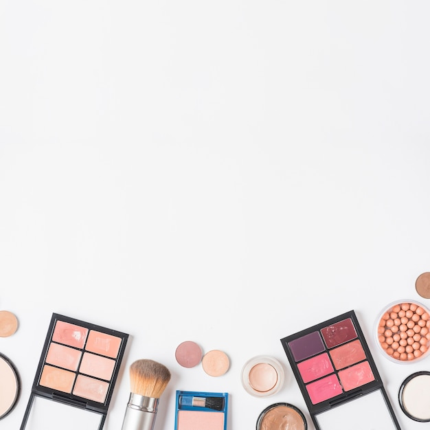 High angle view of makeup kits at the bottom of white backdrop Free Photo
