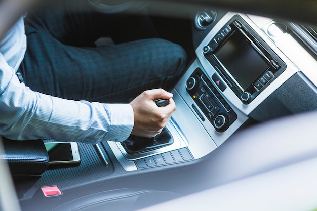 High angle view of a man's hand changing gear in car Free Photo