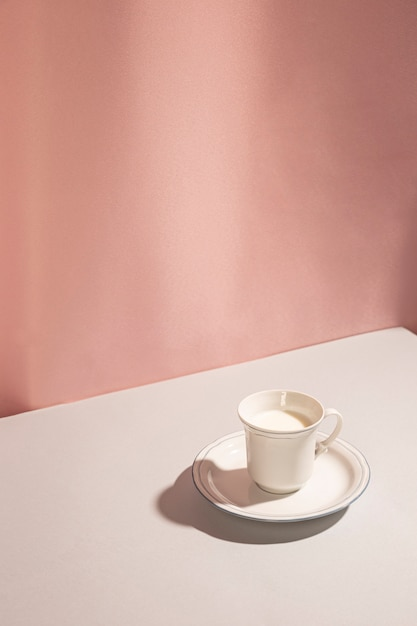 High angle view of milk in cup against pink background Free Photo
