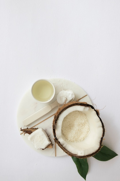 High angle view of moisturizing cream; coconut and oil on white marble board Free Photo