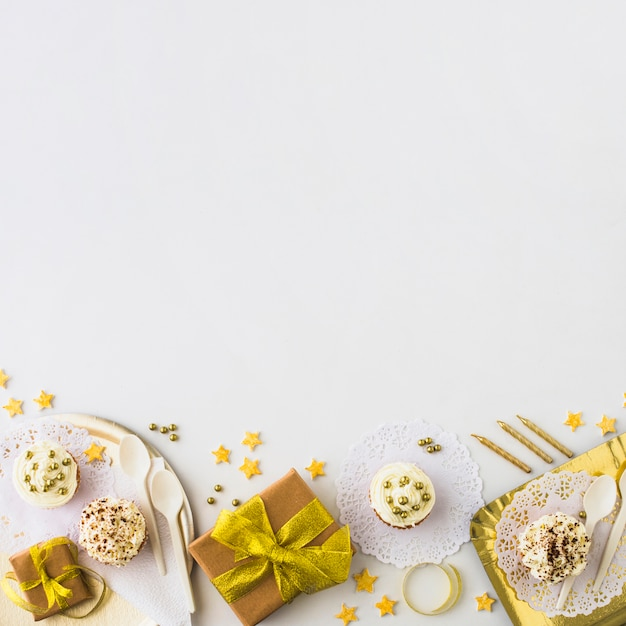 High angle view of muffins and gifts at the edge of white backdrop Free Photo