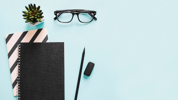 High angle view of notebook; pencil; eraser and spectacles on blue background Free Photo