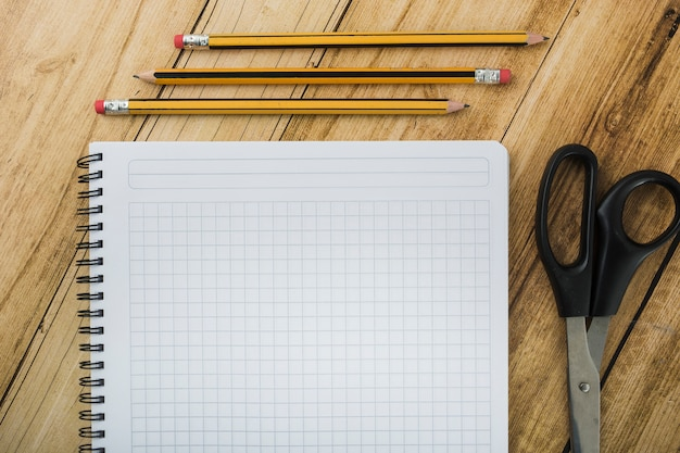 High angle view of notepad; scissors and pencils on wooden backdrop Free Photo