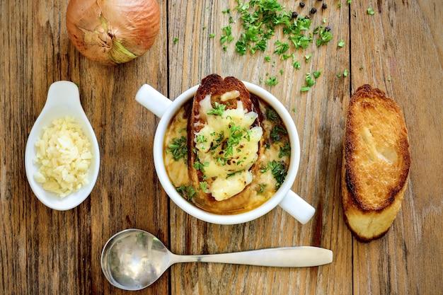 ライトの下でテーブルの上のスープとグリルしたパンのボウルの高角度のビュー 無料写真