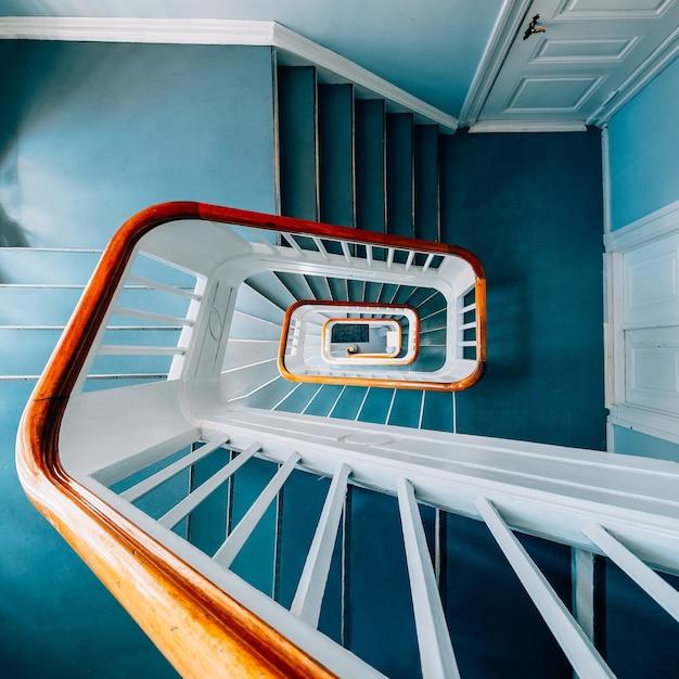 Высокий угол обзора современной винтовой лестницы на выставке под светом Бесплатные Фотографии