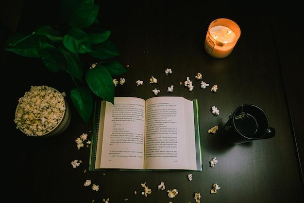 火のともったろうそくとお茶とテーブルの上の開いた本とポップコーンの高角度のビュー 無料写真