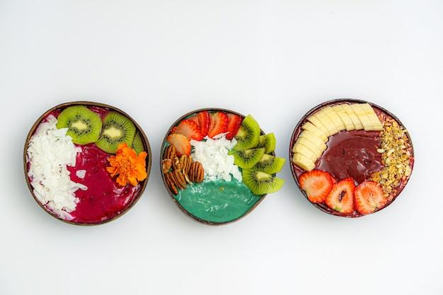 Высокий угол обзора чаш с нарезанными фруктами и соусами на белом столе Бесплатные Фотографии