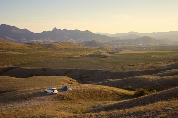 그림 같은 산 풍경에 캠프장의 높은 각도보기. 텐트와 흰색 차가 옆에 주차 된 언덕이 많은 지역에서 야영하는 관광객. 자연, 관광, 여행, 휴가 및 하이킹 개념 무료 사진