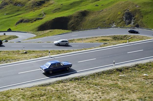 スイスの緑に覆われた丘に囲まれた曲がりくねった道の車のハイアングルビュー 無料写真
