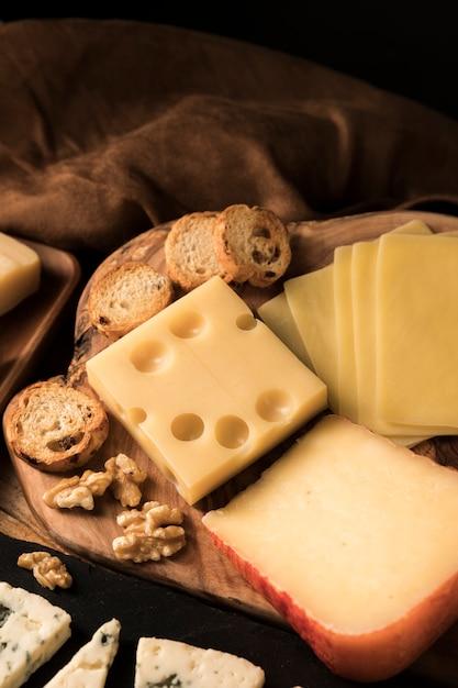 チーズの高角度のビュー。パンのスライスと木製の机の上のクルミ 無料写真