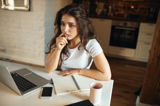 Высокий угол обзора сконцентрированной молодой женщины-учителя, сидящей за столом с портативным компьютером, держащей ручку с задумчивым выражением лица, готовящейся к онлайн-уроку, пишущей от руки в блокноте Бесплатные Фотографии