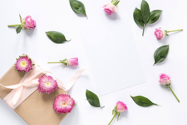 High angle view of flowers and leaves with gift box on white surface Free Photo