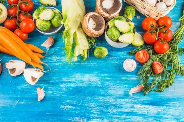 Взгляд высокого угла свежих органических овощей на голубом деревянном фоне Бесплатные Фотографии