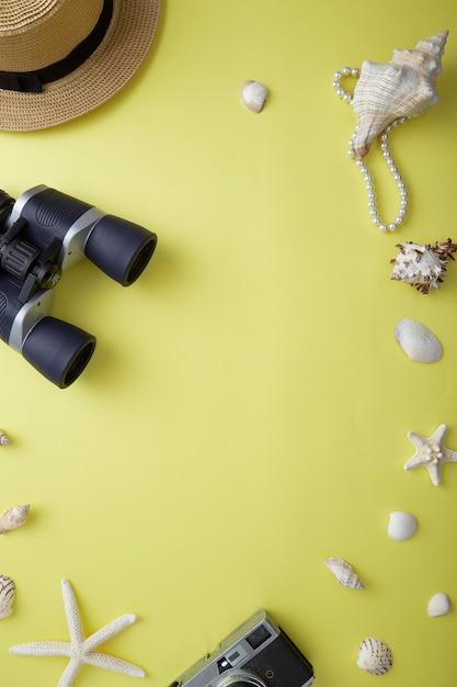 Высокий угол обзора ракушек с помощью бинокля и ювелирных изделий на желтый Premium Фотографии