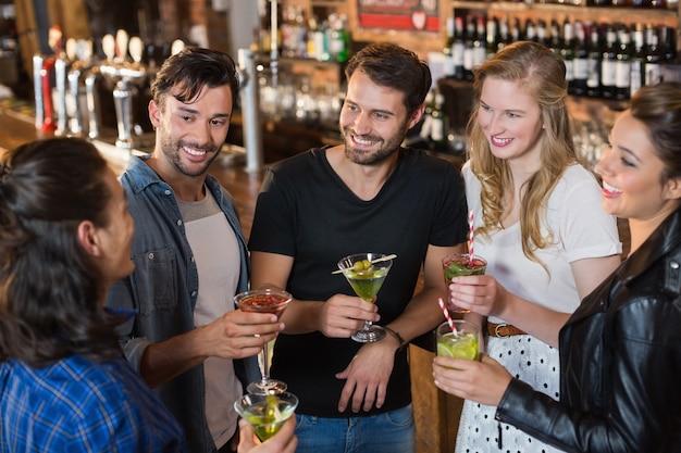 Высокий угол обзора улыбающихся друзей, держащих напитки, стоя вместе Premium Фотографии