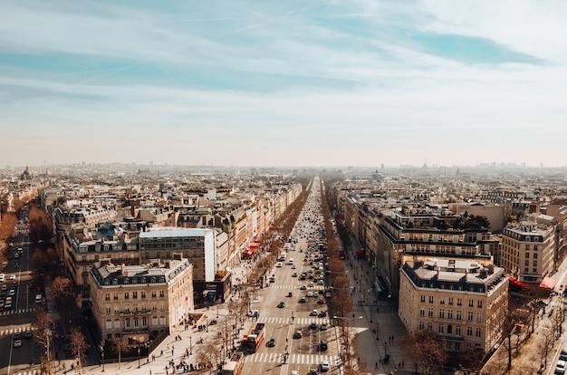Высокий угол обзора елисейских полей под облачным небом и солнечным светом в париже Бесплатные Фотографии