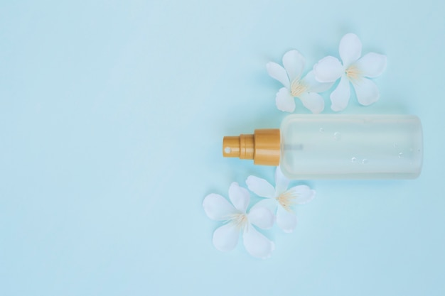 High angle view of perfume bottle with white flowers on blue background Free Photo