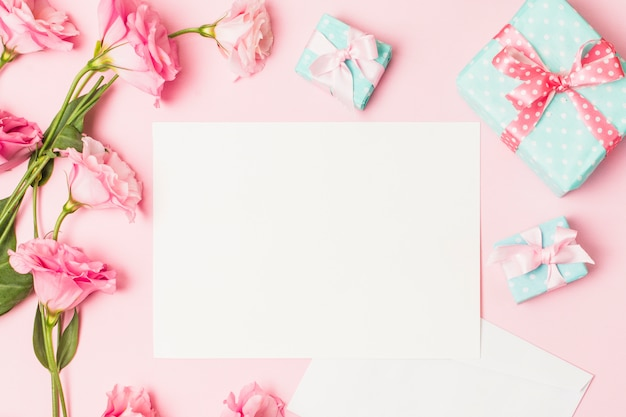 High angle view of pink flower; white blank paper and decorative gift box Free Photo