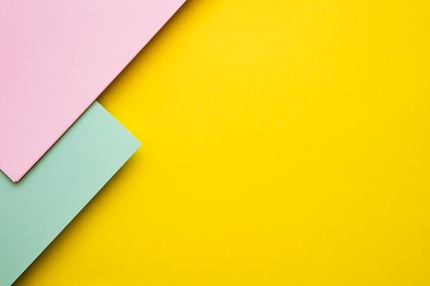 Vista dell'angolo alto delle carte del cartone rosa e verde sul contesto giallo Foto Gratuite