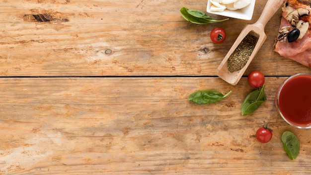 High angle view of pizza slice; herbs; tomato; basil leaf; tomato sauce with cheese on wooden background Free Photo