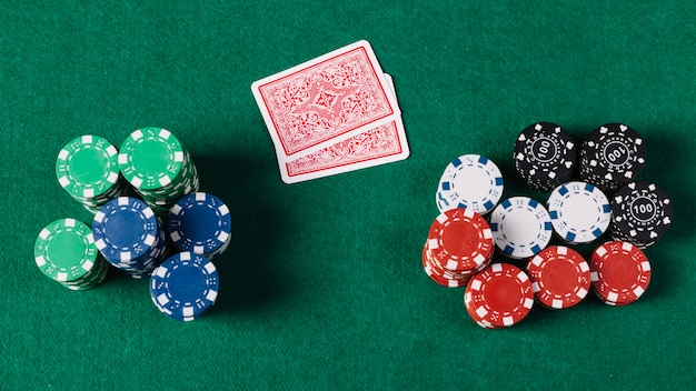 High angle view of playing cards and chips on green poker table Premium Photo