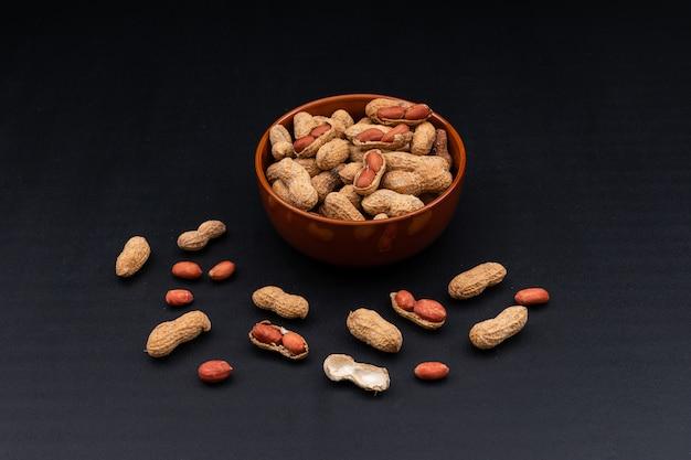High angle view raw peanuts in bowl on dark horizontal Free Photo