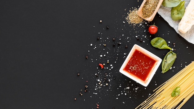 High angle view of raw spaghetti pasta and ingredient on slate backdrop Free Photo