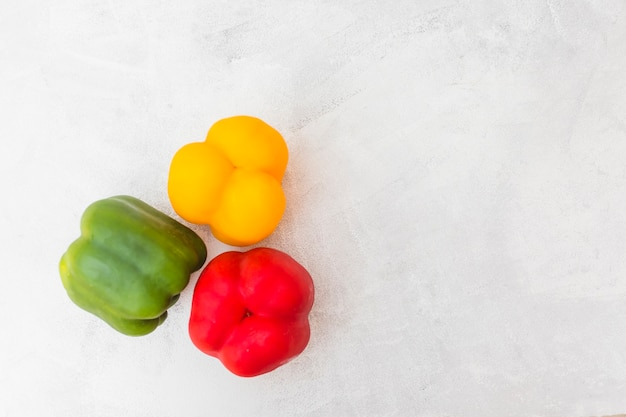 High angle view of red; green and yellow bell peppers on white background Free Photo