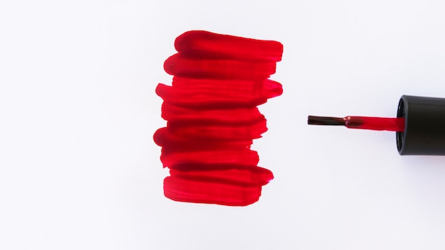 High angle view of red nail varnish strokes and brush on white background Free Photo