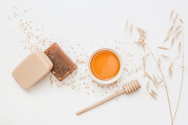 High angle view of soap; honey; honey dipper and hush on white background Free Photo